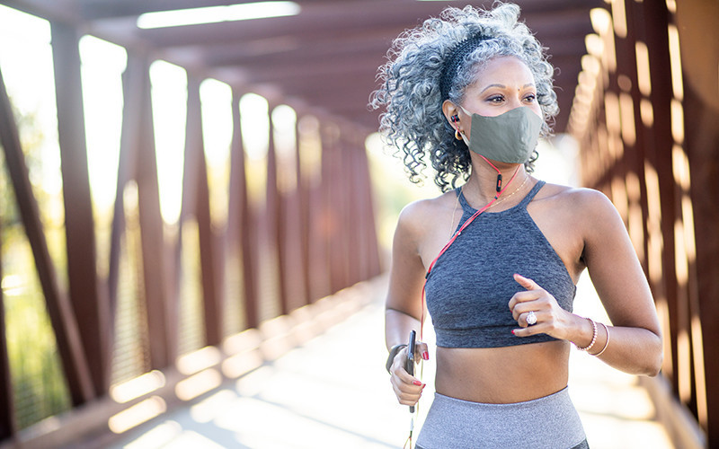 woman jogging outdoors wearing face mask