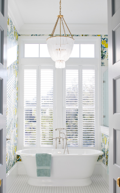 View of a tub in a bathroom with tall windows