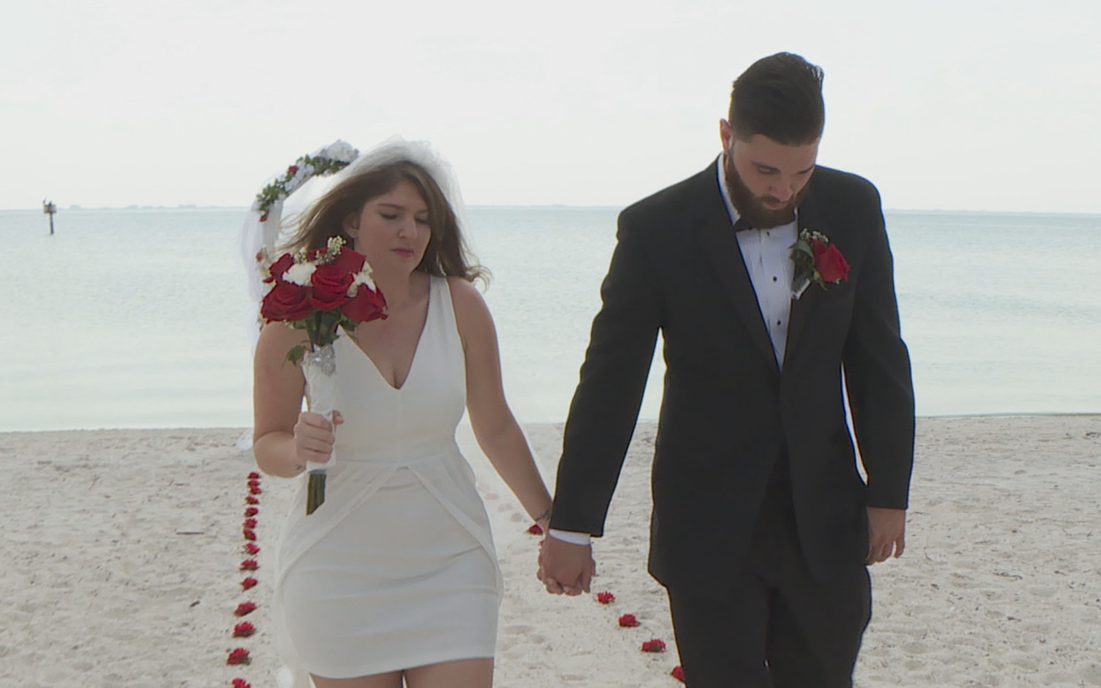 Groom and bride walking hand in hand on a beach