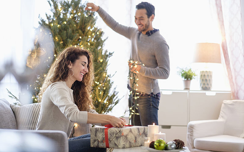 couple decorating tree and gifts together