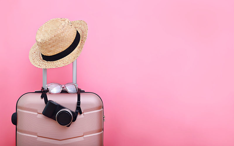 pink suitcase with beach hat, sunglasses and camera hanging on the handle