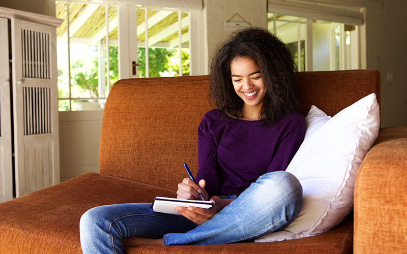 woman writing in journal on couch