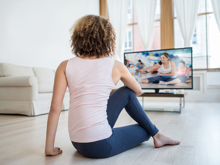 woman exercising with the TV