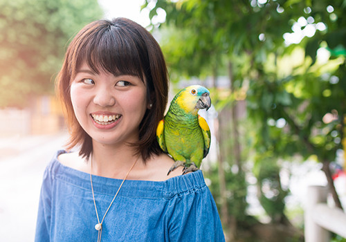 woman with parrot on her shoulder