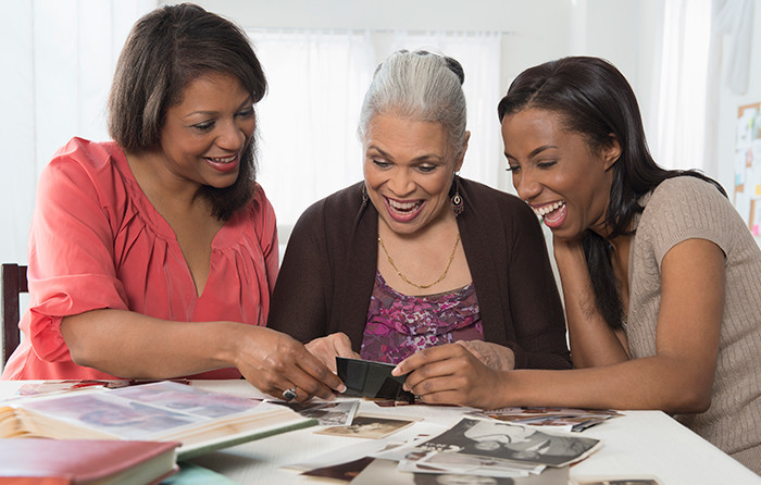 Generations of women looking at pictures and smiling