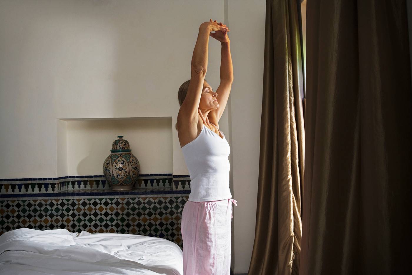 woman stretching by the window