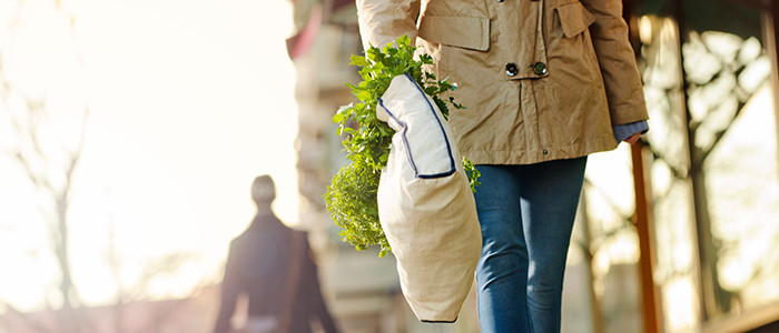 woman walking with plant in bag