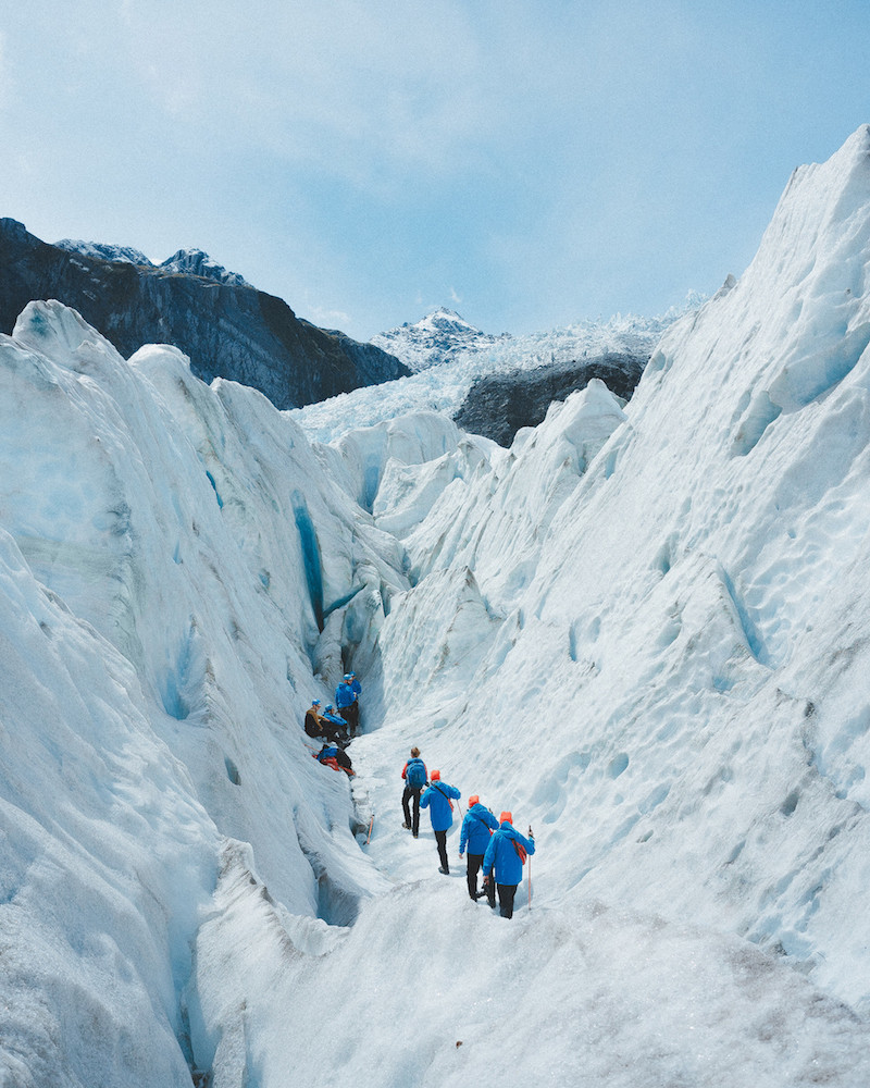 Mountain climbers walking along icy rocks