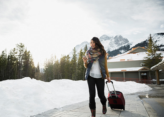woman in snow with luggage