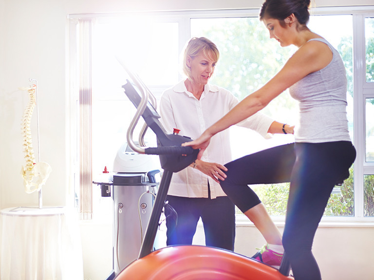 Woman sitting on exercise bike being assisted by a physical therapist