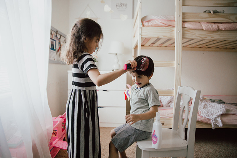 girl brushing siblings hair