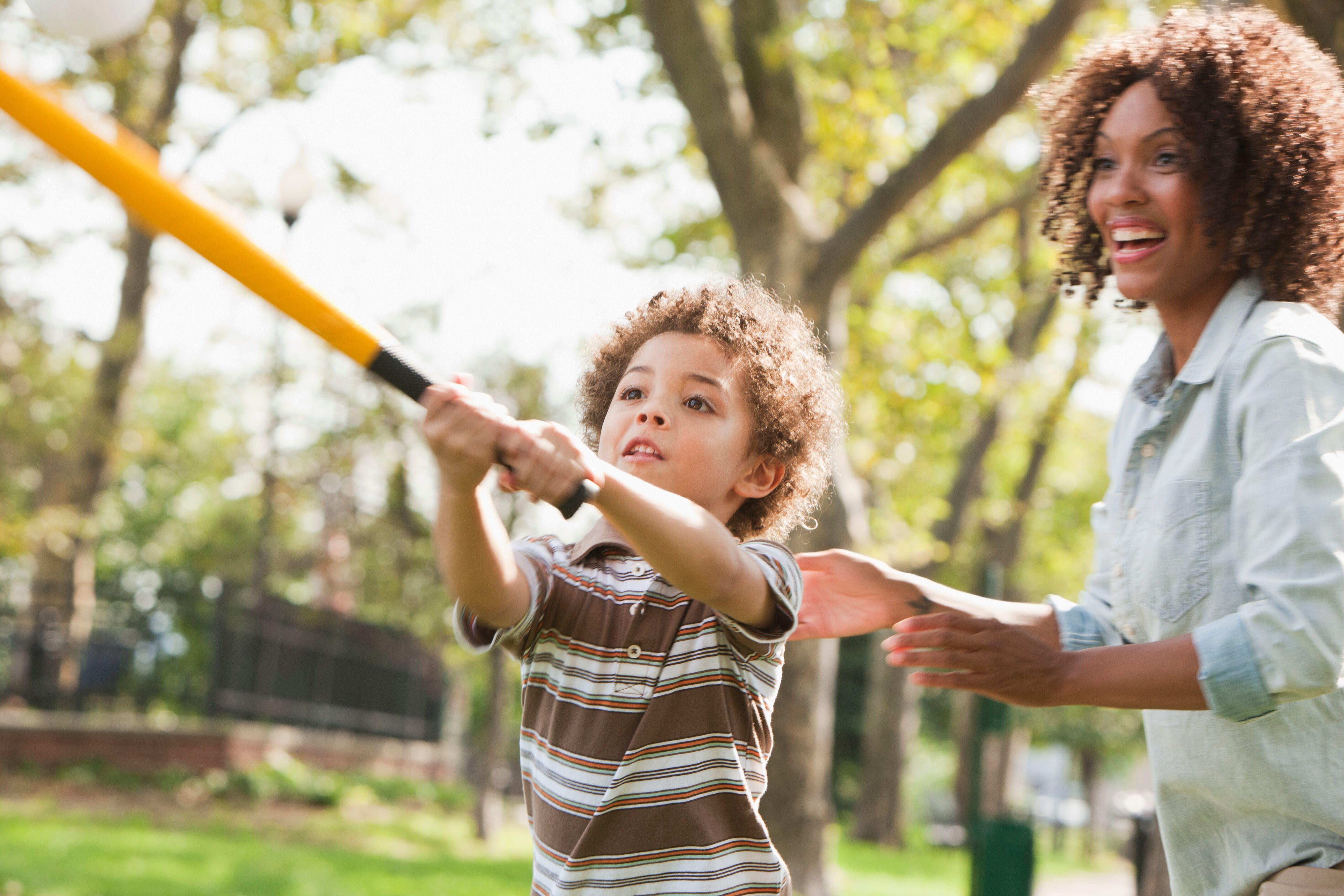 woman playing baseball with son